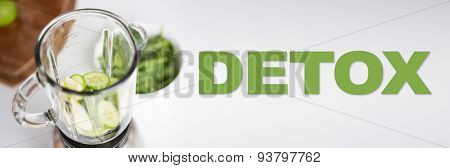healthy eating, cooking, vegetarian food, detox and diet concept - close up of blender jar and green vegetables on table at home
