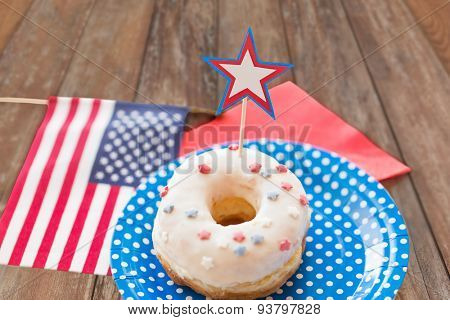 american independence day, celebration, patriotism and holidays concept - close up of glazed donut with american flag and star decoration on disposable plate at party over wooden table background