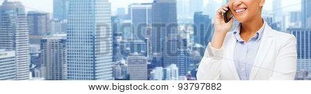 business, people and communication concept - smiling african american businesswoman calling on smart phone over city background