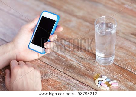 medicine, technology, nutritional supplements and people concept - close up of male hands smartphone, pills and water on table