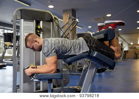 sport, fitness, bodybuilding, lifestyle and people concept - man exercising and flexing muscles on leg curl machine in gym