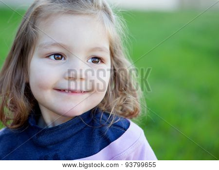Cute little girl with a beautiful smil in the park