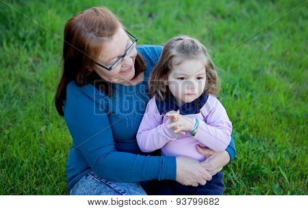 Proud grandmother with her granddaughter sitting on the grass in the field