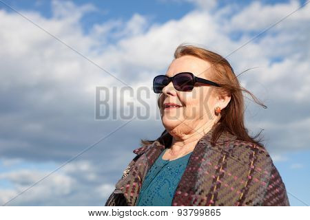 Woman of about sixty years abroad with sunglasses