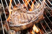 image of flame-grilled  - Grilled pork steaks over flames on the grill - JPG