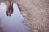 image of paved road  - Bride and groom reflected in slop on paved road - JPG