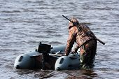 stock photo of hunter  - the hunter pulls the boat from shoal - JPG