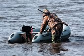 picture of hunter  - the hunter with motor rubber boat on the river - JPG