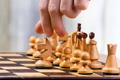 pic of chessboard  - hand of chess player near chessboard with pieces - JPG