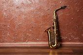 stock photo of saxophones  - Golden saxophone on brown wall background - JPG