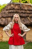 stock photo of national costume  - Young woman in red ukrainian national costume near old historic house - JPG