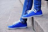image of street-walker  - Female feet in gumshoes on  stone stairs - JPG