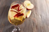 stock photo of cider apples  - Glass of apple cider with fruits on wooden background - JPG