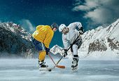 stock photo of ice hockey goal  - Ice hockey player in action outdoor around mountains - JPG