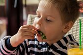 Постер, плакат: The boy has breakfast Kid drinking orange juice