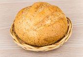 image of buckwheat  - Round fresh buckwheat bread in wicker basket on wooden table - JPG