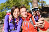 picture of two women taking cell phone  - Selfie couple using smart phone camera taking photo hiking in nature with smartphone - JPG