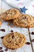 pic of baked raisin cookies  - Oatmeal raisin cookies on a table with a printed tea towel in the background - JPG