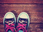 pic of pink shoes  - a wide angle photo of a pair of shoes with pink shoe laces on a vintage wooden background toned with a retro vintage instagram filter app - JPG