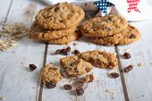 image of baked raisin cookies  - Oatmeal raisin cookies on a table with a printed tea towel in the background - JPG