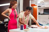 image of tailoring  - designer asian man tailor shop working on table with woman customer fashion dress clothes - JPG