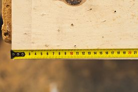 pic of measurement  - Yellow shabby tape measure on a chipdeck in workshop on a workbench measuring wooden product - JPG