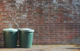 picture of dustbin  - trash can rubbish dustbin outside by brick wall with copy space - JPG