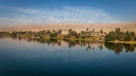 image of greenery  - Palm trees and greenery reflecting on the Nile river with mountains in background - JPG