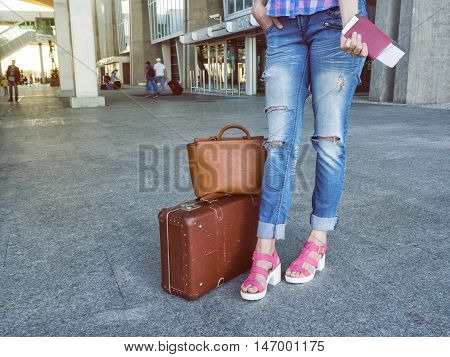 Attractive woman at the airport with retro vintage luggage. In his hand passport with the ticket. The concept of tourism holiday vacation migration