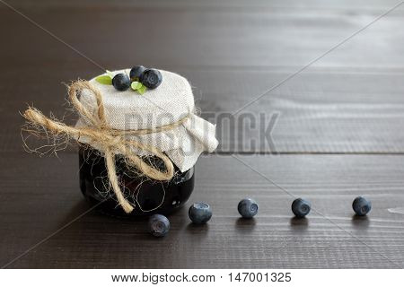 Glass jar of berry jam with fresh berries blueberries / sweet rarity delicacy made from wild berries