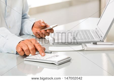 Unrecognizable Man Is Working By Using A Calculator And Phone
