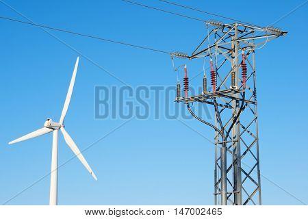 Windmill for electric power production and pylon, La Muela, Zaragoza Province, Aragon, Spain.