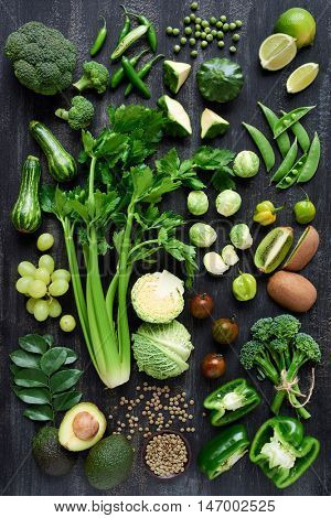 Spread of fresh green produce on dark rustic distressed background, broccoli, celery, beans, capsicum, peppers, peas, brussels sprouts, kiwi, avocado, grapes