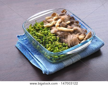 boiled oyster mushroom and cowslip creeper in clear bowl and was placed on the blue tablecloth