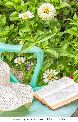 Relax with a book in the garden on a sunny summer day. Green chaise lounge a white hat and book on a background of flowering flowerbed