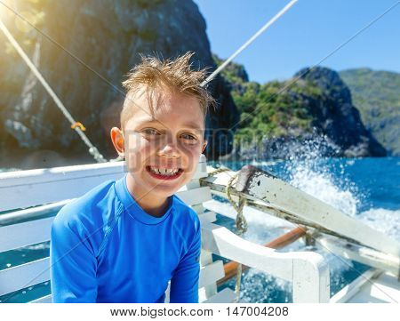 Cute boy on a boat at a sunny summer day. Philippines
