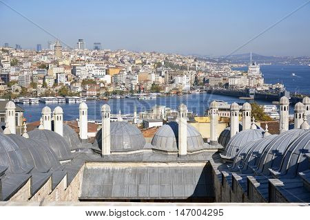 Istanbul, Turkey - November 4, 2015. View over Galata bridge in Istanbul from the terrace of Suleymaniye mosque, with chimneys and roof in the form of small domes, Golden Horn inlet, residential and commercial buildings.