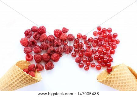 a plurality of raspberries and currants spill out of waffle cones in form of two red hearts / appetizing sweet love