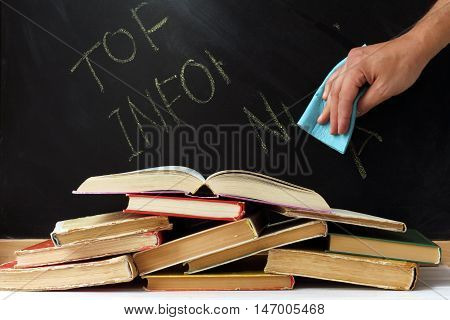 hand with a cloth removes inscriptions made with chalk on a blackboard background stack of old books / erasing important information