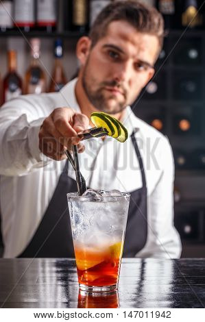Young Barman decorating fruit cocktail with lime