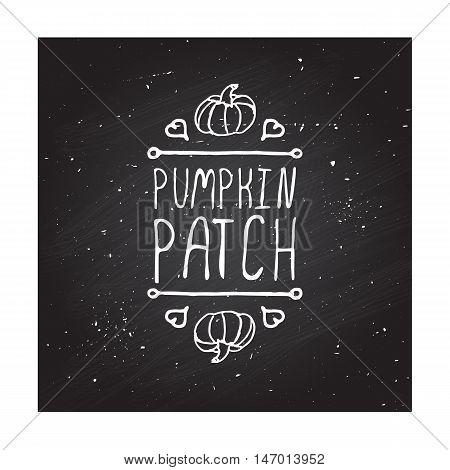 Hand-sketched typographic element with pumpkin, maple leaves and text on blackboard background. October