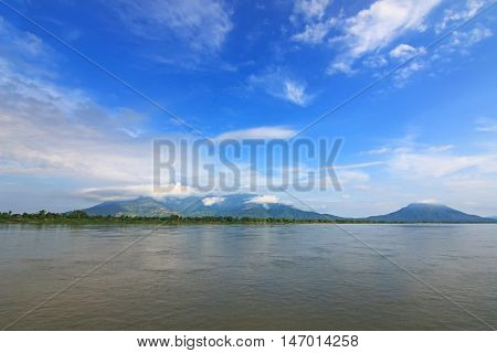 View of Mekong river with background of green mountain and blue sky in southern Laos