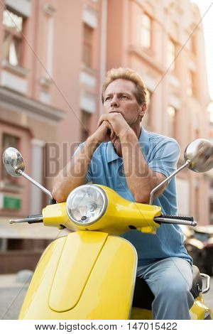Mature guy sitting on scooter. Thoughtful man on street background. Which direction to ride. Time to improvise.