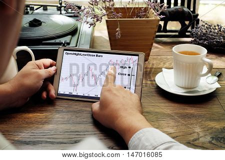 Tablet computer with stock analytics and abstract graphs in man hands. Reading charts document in cafe. Business man working out of office.
