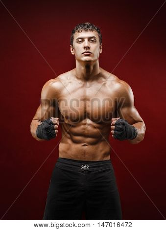 Portrait of topless young muscular man in fighting gloves on red background