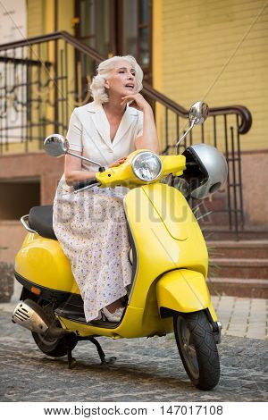 Mature woman sitting on scooter. Lady with dreamy face. First travel to another city. Road is waiting.