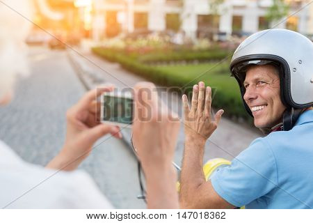 Man waving hand at camera. Lady holding photo camera. Never felt happier than now. My trip through Europe.