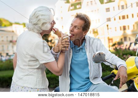 Mature couple eats ice cream. Man is looking at lady. Tourists are enjoying their dessert. Season of fun.