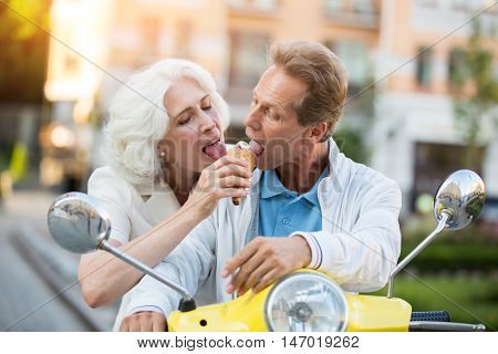 Mature couple sharing ice cream. People are sitting on scooter. Enjoy what you have today. Unforgettable summer tour.