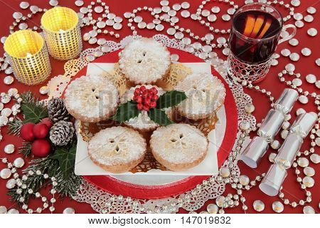 Christmas food and drink still life with mince pie cakes, holly, mulled wine, bauble decorations, silver crackers and candles over red background.